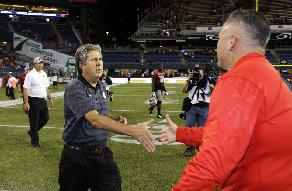 Photo - Washington State Washington State head coach Mike Leach, left, shakes hands with Rutgers head coach Kyle Flood, right, after an NCAA college football game, Thursday, Aug. 28, 2014, in Seattle. Rutgers beat Washington State 41-38. (AP Photo/Ted S. Warren)