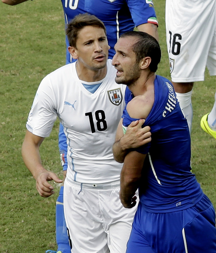 Photo - Italy's Giorgio Chiellini, right, shows his shoulder after colliding with Uruguay's Luis Suarez's mouth as Uruguay's Gaston Ramirez (18) watches during the group D World Cup soccer match between Italy and Uruguay at the Arena das Dunas in Natal, Brazil, Tuesday, June 24, 2014. (AP Photo/Hassan Ammar)