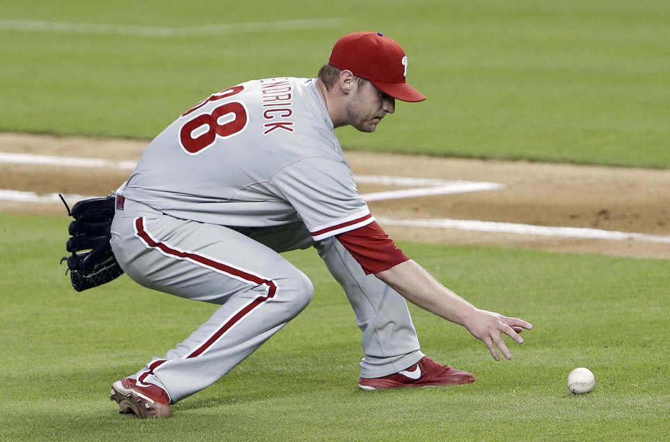 Photo - Philadelphia Phillies starting pitcher Kyle Kendrick fields a ball bunted by Miami Marlins' Brad Hand during the fifth inning of a baseball game on Thursday, July 3, 2014, in Miami. Hand was thrown out at first base. (AP Photo/Wilfredo Lee)