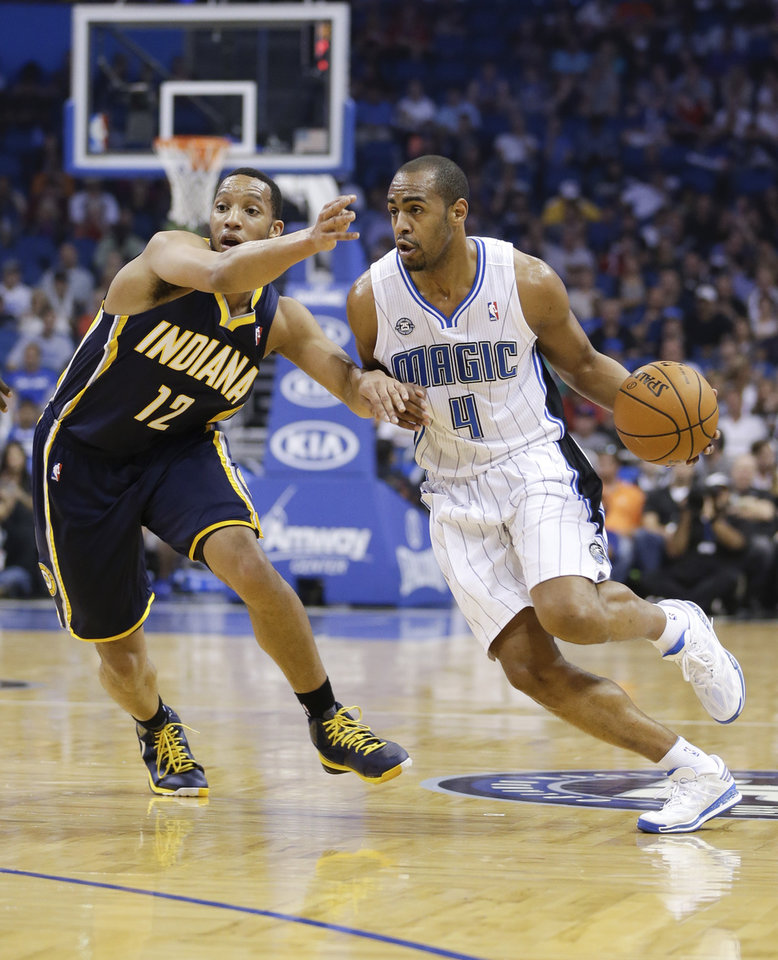 Photo - Orlando Magic's Arron Afflalo (4) drives around Indiana Pacers' Evan Turner (12) during the first half of an NBA basketball game in Orlando, Fla., Wednesday, April 16, 2014. (AP Photo/John Raoux)