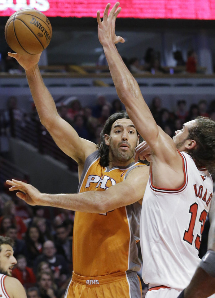 Photo - Phoenix Suns forward Luis Scola, left, passes the ball against Chicago Bulls center Joakim Noah during the first half of an NBA basketball game in Chicago on Saturday, Jan. 12, 2013. (AP Photo/Nam Y. Huh)
