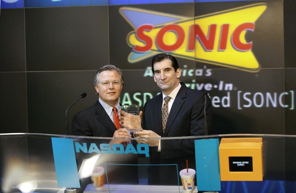 Photo - Sonic Chairman Cliff Hudson, left, kicks off Nasdaq trading to celebrate the opening of the company's 3,000th drive-in. With him is Robert Greifeld, Nasdaq president and chief executive officer.
