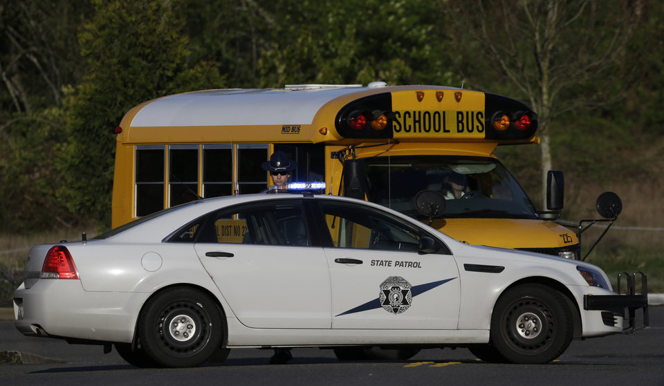 Photo - A school bus turns around after encountering a Washington State Patrol trooper staffing a roadblock about a block from the scene of an overnight shooting that left five people dead, Monday, April 22, 2013, at an apartment complex in Federal Way, Wash. (AP Photo/Ted S. Warren)