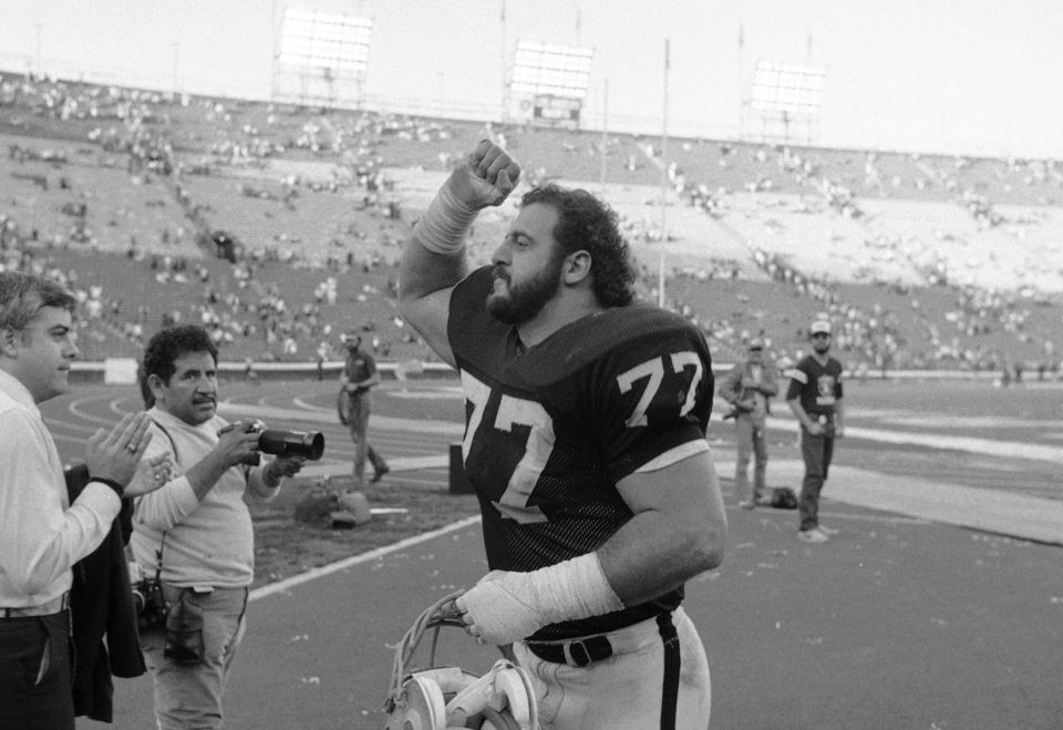 FILE - In this Jan. 2, 1984, file photo, Los Angeles Raiders Lyle Alzado gives a fist of victory after the Raiders beat the Pittsburgh Steelers in playoff fooball game in Los Angeles. With uneven testing for steroids and inconsistent punishment, college football players are packing on significant weight _ in some cases, 30 pounds or more in a single year _ without drawing much attention from their schools or the NCAA in a sport that earns tens of billions of dollars for teams Football's most infamous steroid user was Alzado, who became a star NFL defensive end in the 1970s and 80s before he admitted to juicing his entire career. He started in college, where the 190-pound freshman gained 40 pounds in one year. It was a 21 percent jump in body mass, a tremendous gain that far exceeded what researchers have seen in controlled, short-term studies of steroid use by athletes. Alzado died of brain cancer in 1992. (AP Photo, File)