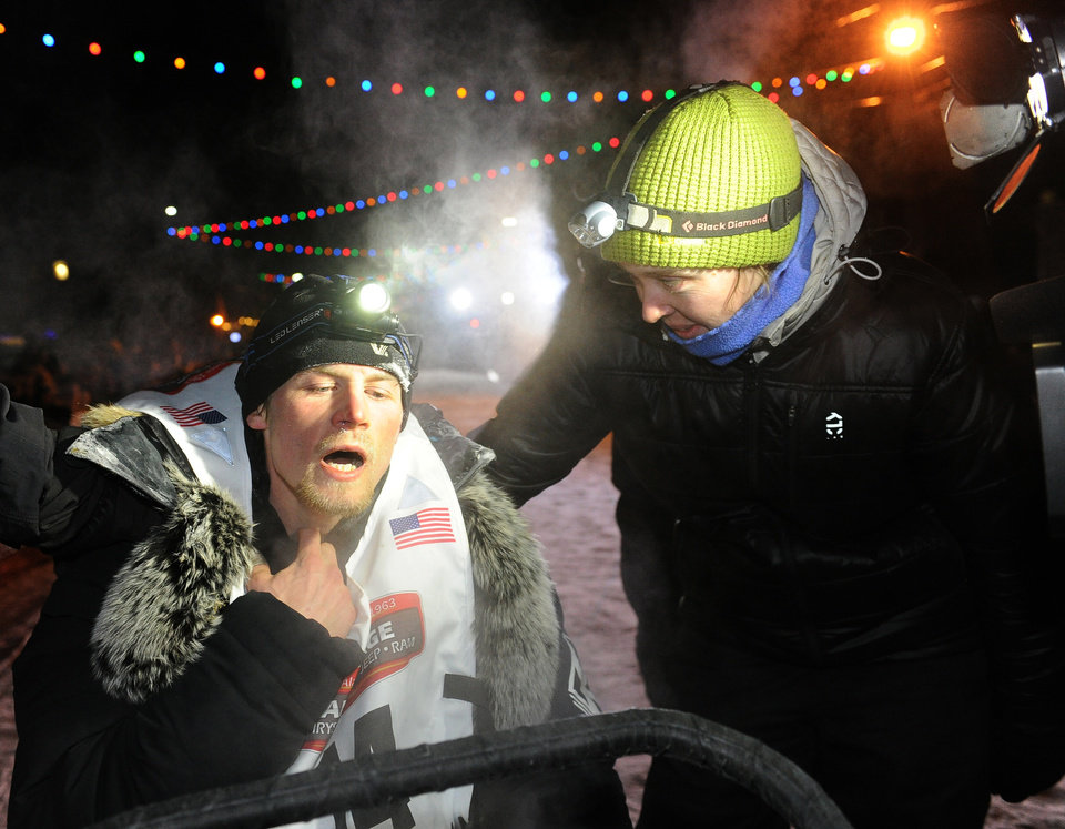 Photo - Dallas Seavey, left, reacts after finishing the 2014 Iditarod Trail Sled Dog Race in Nome, Alaska, Tuesday, March 11, 2014. Seavey ran a blistering pace to rally from third place and win his second Iditarod in a record-breaking finish, after a sudden storm blew the front-runner out of the competition and kept another musher minutes away from her first win.  (AP Photo/The Anchorage Daily News, Bob Hallinen)  LOCAL TV OUT (KTUU-TV, KTVA-TV) LOCAL PRINT OUT (THE ANCHORAGE PRESS, THE ALASKA DISPATCH)