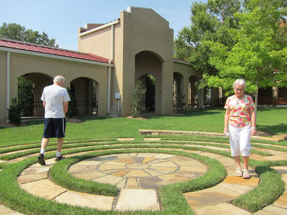 Photo - Malcolm and Kathy May, of Bethany, walk the four-circuit labyrinth in the east garden of St. Paul's Episcopal Cathedral during the recent