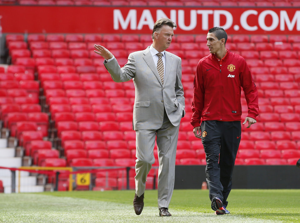 Photo - Manchester United's new player Angel Di Maria, right, and manager Louis van Gaal, pose for photographers, at Old Trafford Stadium in Manchester, England, Thursday, Aug. 28, 2014. Manchester United have signed winger Angel Di Maria from Real Madrid for a British record transfer fee of £59.7m. The Argentine winger had a medical in Manchester on Tuesday and has signed a five-year deal. (AP Photo/Alastair Grant)