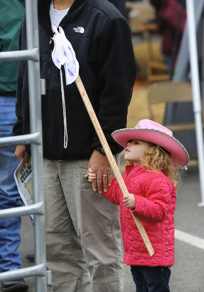 """Marisa Glenn, 3, of Edmond, holds her stick horse while waiting in line to ride a pony. Children with their parents endured cold temperatures and intermittent rain to come to the grounds of the Oklahoma History Center on Saturday, March 23, 2013, to participate in the 3rd annual Cowboy Round-up,  billed to be a  """"rendezvous with adventure.""""  Cowboys and chuck wagons were on hand to bring the cattle drive era to life for visitors of all ages. Special activities included pony rides, stick-horse races, roping demonstrations, branding,  a medicine man show, biscuits made from scratch and cooked in Dutch ovens, and a chance for children to make a braided rope they could take with them as a souvenir.  Youth were encouraged to dress the part as many did, wearing boots, vests, bandanas, chaps,and cowboy hats.    Photo by Jim Beckel, The Oklahoman"""