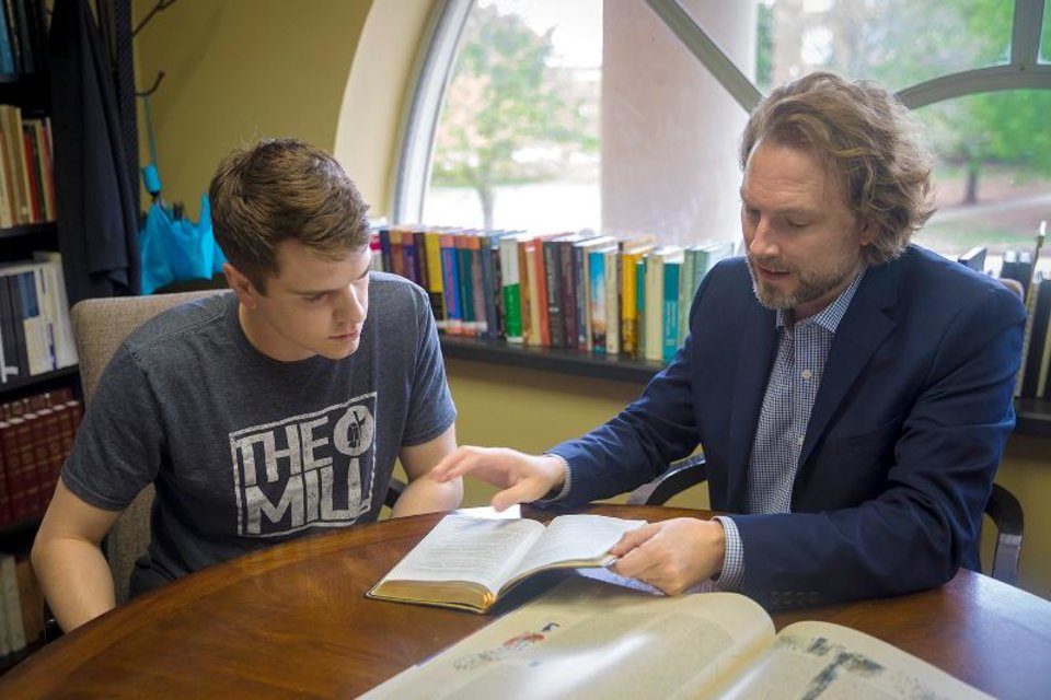 Photo - Dean Heath Thomas (right) examines the scriptures with a student in OBU's Hobbs College of Theology and Ministry. (Photo provided)