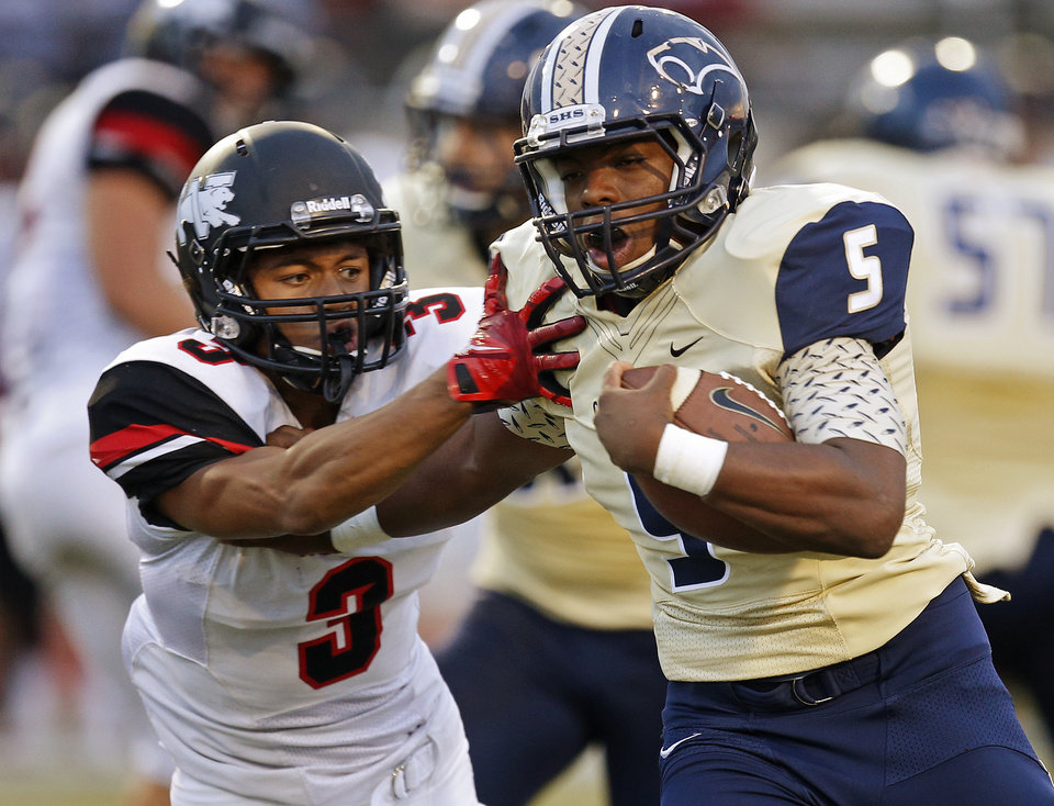 Photo - Southmoore's Pierce Speed fights off Westmoore's Cassius Hill during their high school football game in Moore, Okla., Friday, Sept. 13, 2013. Photo by Bryan Terry, The Oklahoman
