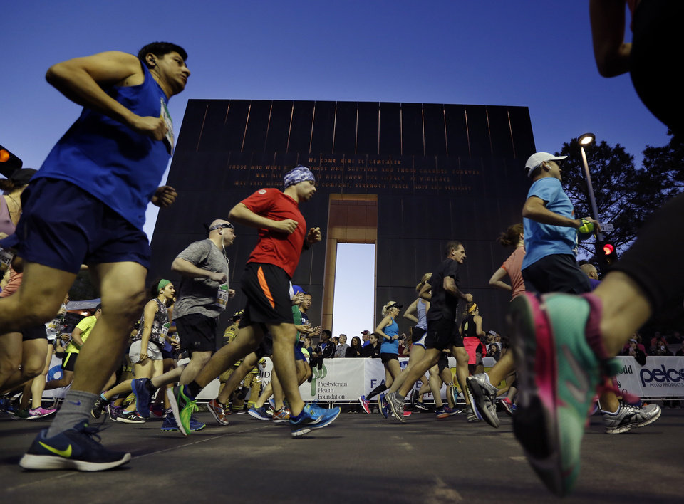 Photo - Runners stream past the 9:03 gate during the Oklahoma City Marathon in Oklahoma City,  Sunday, April 29, 2018. Photo by Sarah Phipps, The Oklahoman