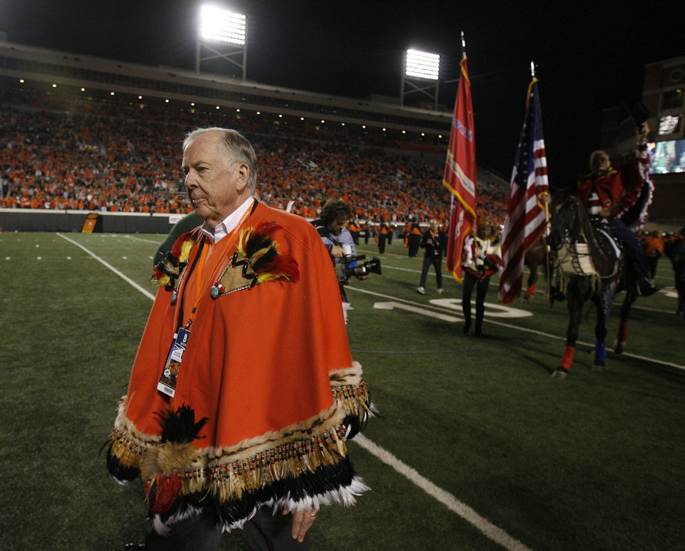 Photo - Boone Pickens leads horses from the Wild Horse Foundation off the field during halftime of the college football game between Oklahoma State University (OSU) and the University of Colorado (CU) at Boone Pickens Stadium in Stillwater, Okla., Thursday, Nov. 19, 2009. Photo by Sarah Phipps, The Oklahoman