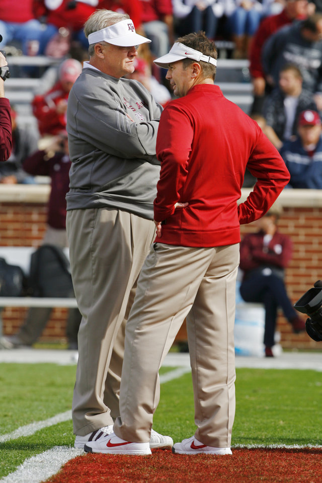 Photo - Texas A&M head coach Mike Sherman (left) and Sooner head coach Bob Stoops talk before the college football game between the Texas A&M Aggies and the University of Oklahoma Sooners (OU) at Gaylord Family-Oklahoma Memorial Stadium on Saturday, Nov. 5, 2011, in Norman, Okla. Photo by Steve Sisney, The Oklahoman