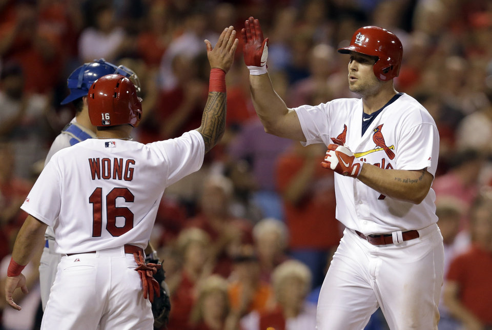 Photo - St. Louis Cardinals' Matt Holliday, right, is congratulated by Kolten Wong after hitting a two-run home run during the fifth inning of a baseball game against the Los Angeles Dodgers on Friday, July 18, 2014, in St. Louis. (AP Photo/Jeff Roberson)