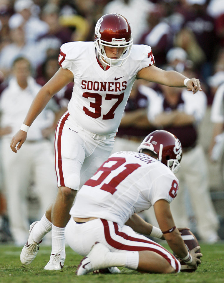 Photo - OU's Matthew Moreland kicks a failed field goal attempt as Carter Whitson holds in the second quarter during the college football game between the University of Oklahoma (OU) and Texas A&M University (TAMU) at Kyle Field in College Station, Texas, Saturday, Nov. 8, 2008. BY NATE BILLINGS, THE OKLAHOMAN