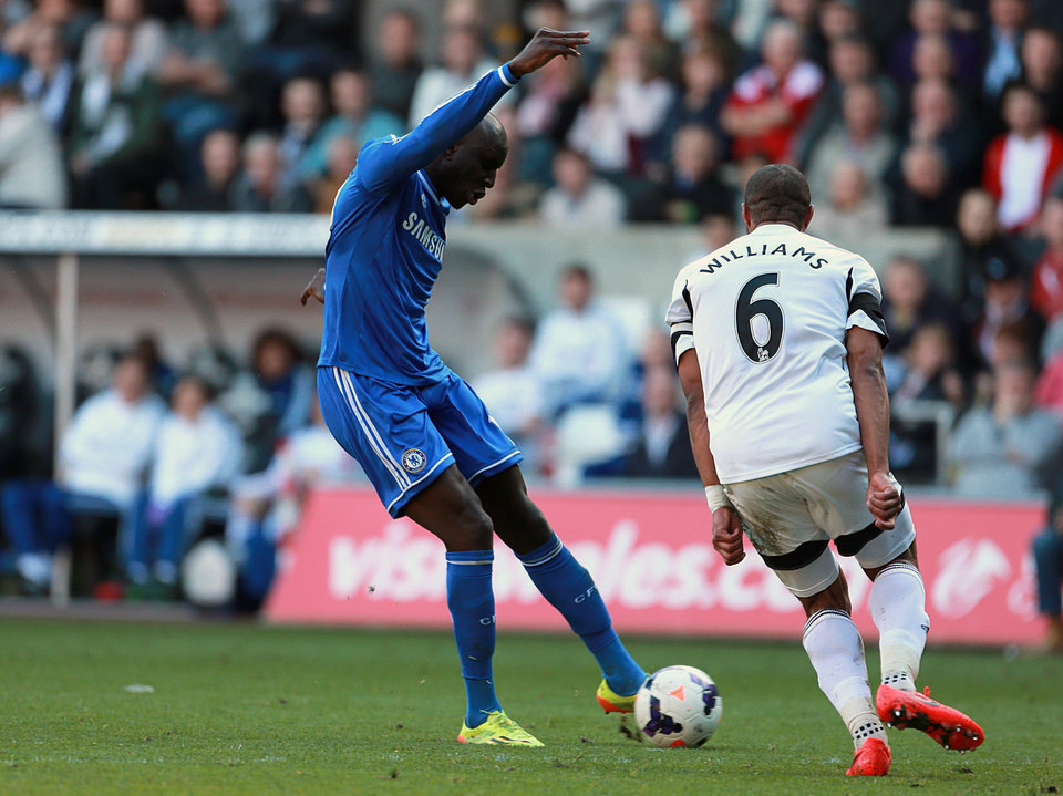 Photo - Chelsea's Demba Ba, left, scores his teams opening goal during their English Premier League soccer match against Swansea City at the Liberty Stadium, Swansea, Wales, Sunday, April 13, 2014. (AP Photo/David Davies, PA Wire)    UNITED KINGDOM OUT   -   NO SALES   -   NO ARCHIVES