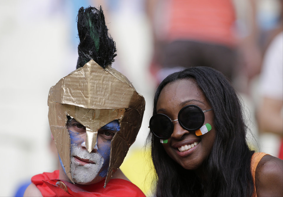 Photo - A Greece and an Ivory Coast supporter pose for a photograph prior to the group C World Cup soccer match between Greece and Ivory Coast at the Arena Castelao in Fortaleza, Brazil, Tuesday, June 24, 2014. (AP Photo/Fernando Llano)