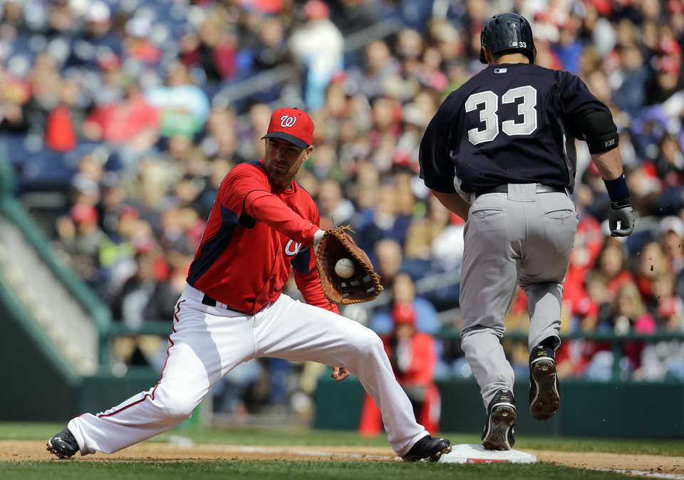 Photo - Washington Nationals first baseman Adam LaRoche (25) catches the throw from third baseman Ryan Zimmerman (11), but New York Yankees designated hitter Travis Hafner (33) is safe at first during the fourth inning of an exhibition baseball game at Nationals Park Friday, March 29, 2013, in Washington. (AP Photo/Alex Brandon)