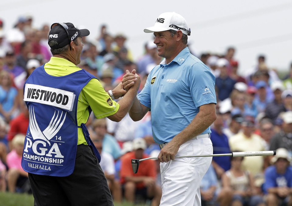 Photo - Lee Westwood, of England, right, shakes hand with his caddie after firing a 6-under par first round of the PGA Championship golf tournament at Valhalla Golf Club on Thursday, Aug. 7, 2014, in Louisville, Ky. (AP Photo/David J. Phillip)