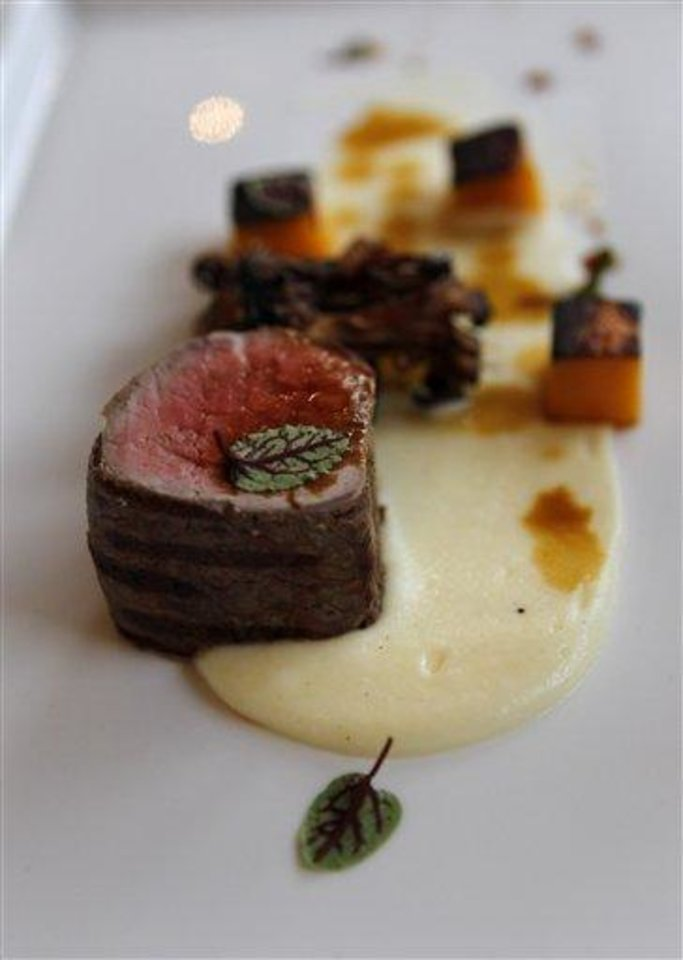 In this Dec. 7, 2012 photo, grilled prime tenderloin with potato butter, fried maitake mushroom, confit winter squash, jus, by executive chef Kristin Butterworth, is seen at the Grill Room of the Windsor Court Hotel in New Orleans. Roughly 50 restaurants in New Orleans are reviving an old Creole custom called reveillon, which stems from the old French tradition of eating a lavish meal after midnight Mass on Christmas Eve. (AP Photo/Gerald Herbert)