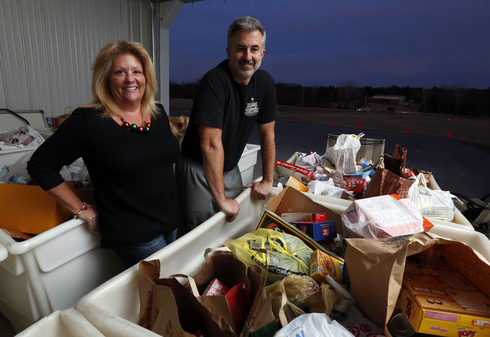 Photo - Kim and Chuck Downs of Norman stand next to one of seven large bins nearly filled with food donated by the community in response to the Downs Family Christmas Light Fight. The family will be featured on Dec. 23 on ABC's