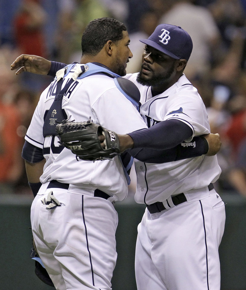 Photo -   Tampa Bay Rays relief pitcher Fernando Rodney, right, hugs catcher Jose Molina after closing out the Los Angeles Angels during the ninth inning of a baseball game, Wednesday, April 25, 2012, in St. Petersburg, Fla. The Rays won the game 3-2. (AP Photo/Chris O'Meara)