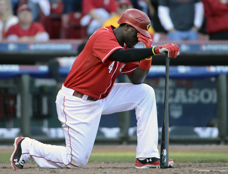 Photo -   Cincinnati Reds' Brandon Phillips kneels at home plate after making the first out in the ninth inning of Game 5 of the National League division baseball series against the San Francisco Giants, Thursday, Oct. 11, 2012, in Cincinnati. The Giants won 6-4 and advanced to the NL championship series. (AP Photo/Michael Keating)