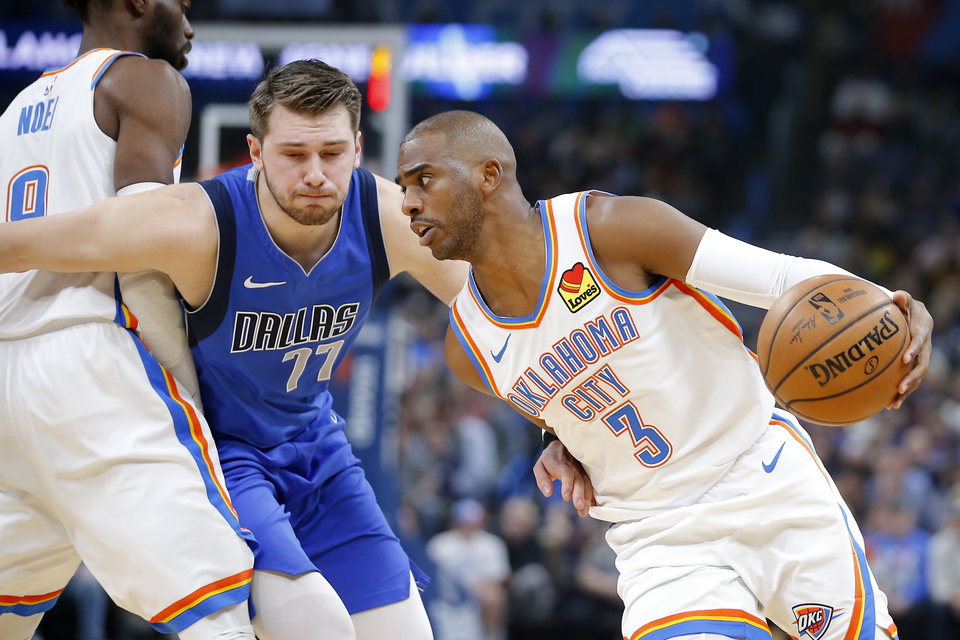 Photo - Oklahoma City's Chris Paul (3) goes past Luka Doncic (77) of Dallas during an NBA basketball game between the Oklahoma City Thunder and the Dallas Mavericks at Chesapeake Energy Arena in Oklahoma City, Tuesday, Dec. 31, 2019. [Bryan Terry/The Oklahoman]