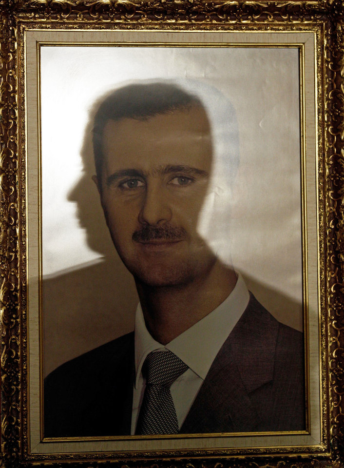 The profile of a Syrian embassy employee is reflected in a framed image of Syria's President Bashar al-Assad at a local Venezuelan hotel, in Caracas, Tuesday, Nov. 27, 2012. The framed image was brought to the local hotel to serve as a backdrop for the news conference held by Syria's Deputy Foreign Minister Faisal al-Mokdad where he was to discuss a message for President Hugo Chavez from Syria's government. (AP Photo/Fernando Llano)