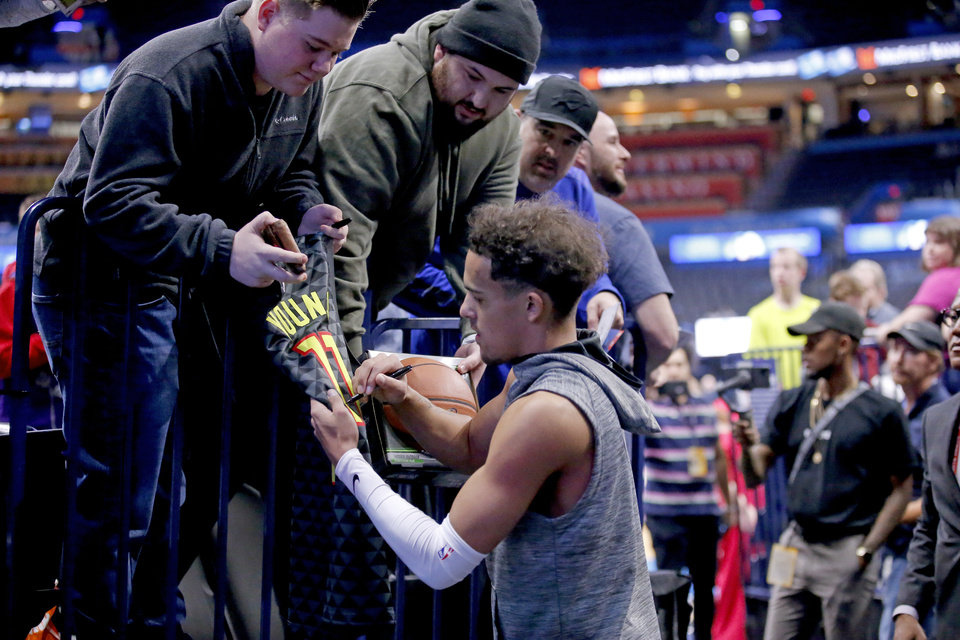 Photo - Atlanta's Trae Young (11) signs autographs for fans before the NBA basketball game between the Oklahoma City Thunder and the Atlanta Hawks at the Chesapeake Energy Arena in Oklahoma City,Friday, Jan. 24, 2020.  [Sarah Phipps/The Oklahoman]