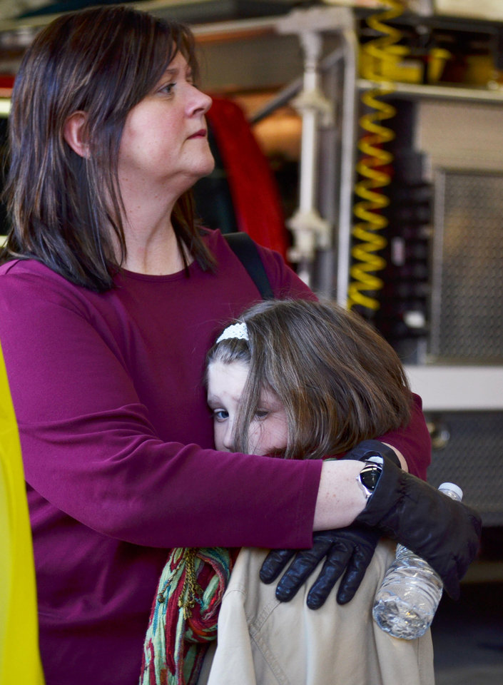 Photo - A mother hugs her daughter following a shooting at the Sandy Hook Elementary School in Newtown, Conn., about 60 miles (96 kilometers) northeast of New York City, Friday, Dec. 14, 2012. An official with knowledge of Friday's shooting said 27 people were dead, including 18 children. It was the worst school shooting in the country's history. (AP Photo/The New Haven Register, Melanie Stengel)   ORG XMIT: CTNHR104