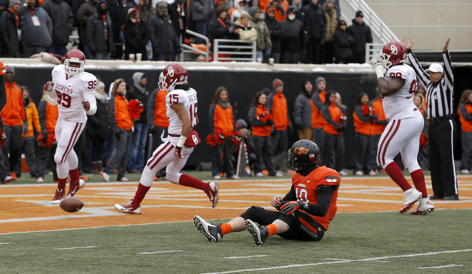 Photo - Oklahoma State's Clint Chelf (10) sits on the ground as OU scores on the last play of the game during the Bedlam college football game between the Oklahoma State University Cowboys (OSU) and the University of Oklahoma Sooners (OU) at Boone Pickens Stadium in Stillwater, Okla., Saturday, Dec. 7, 2013. Oklahoma won 33-24. Photo by Bryan Terry, The Oklahoman