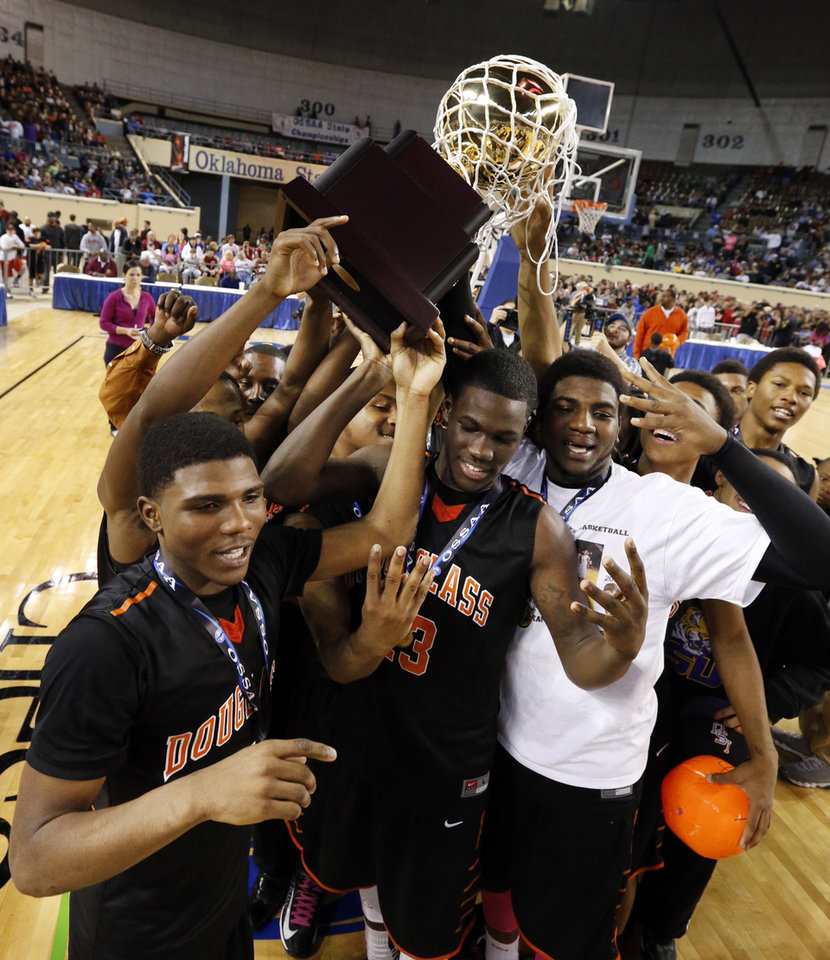 Douglass team members hoist the championship trophy after the 4a boys championship game where the Douglass high school Trojans defeated the Roland Rangers 82-80 at the State Fair Arena on Saturday, March 9, 2013 in Oklahoma City, Okla.  Photo by Steve Sisney, The Oklahoman