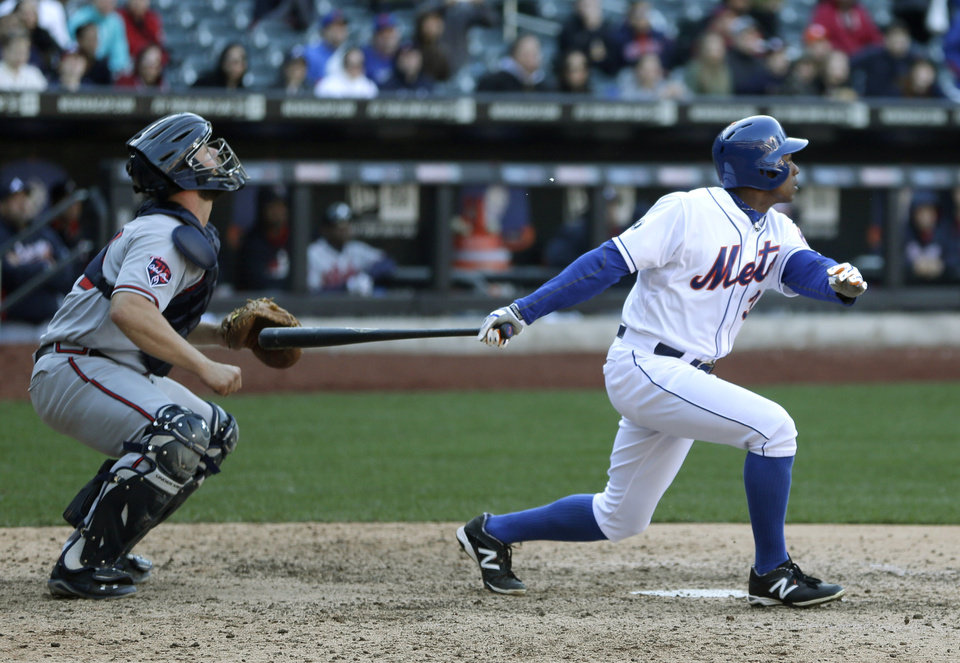 Photo - Atlanta Braves catcher Evan Gattis, left, looks after New York Met's Curtis Granderson's sacrifice fly during the fourteenth inning of the baseball game at Citi Field, Sunday, April 20, 2014 in New York. The Mets defeated the Braves in extra innings 4-3. (AP Photo/Seth Wenig)