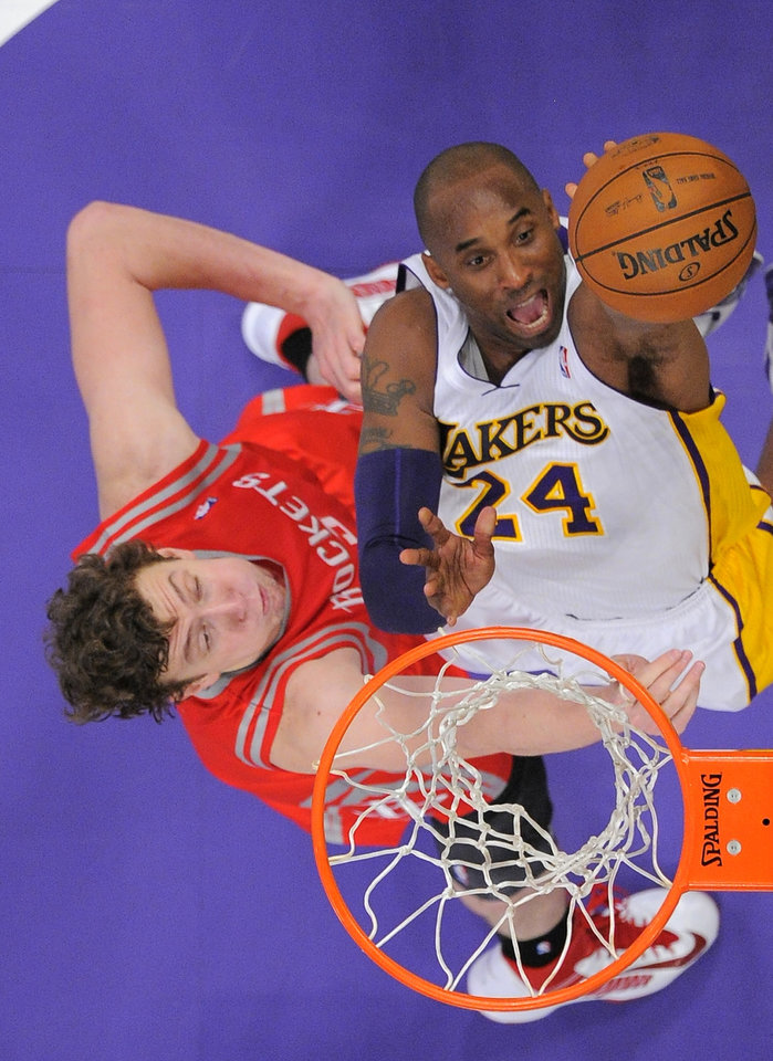 Los Angeles Lakers guard Kobe Bryant, right, puts up a shot as Houston Rockets center Omer Asik, of Turkey, defends during the first half of their NBA basketball game against the Houston Rockets, Sunday, Nov. 18, 2012, in Los Angeles. (AP Photo/Mark J. Terrill)