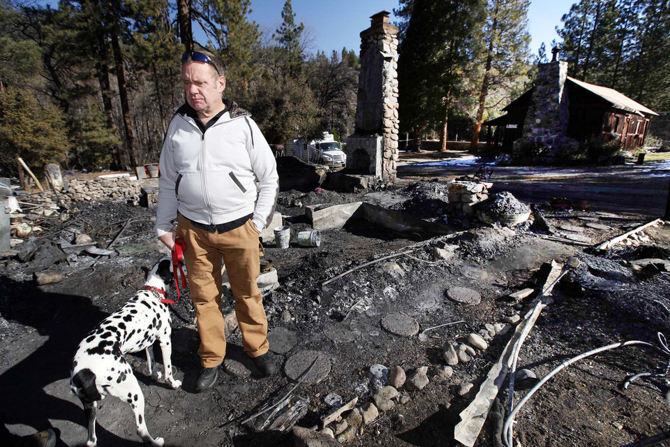 Photo - FILE - In this Friday, Feb. 15, 2013 file photo, Rick Heltebrake, with his dog Suni, looks over the burned-out cabin where Christopher Dorner's remains were found after a police standoff Tuesday near Big Bear, Calif. Dorner took his pickup during his escape attempt. Heltebrake, a ranger who takes care of a Boy Scout camp, was checking the perimeter of the camp for anything out of the ordinary when he saw Dorner emerge from behind some trees. (AP Photo/Nick Ut, FIle)