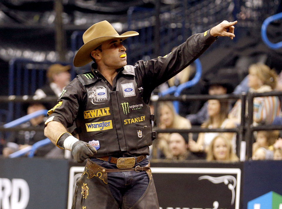 Photo - Guilherme Marchi celebrates a ride during the Express Employment Professionals Invitational PBR  event at the Chesapeake Energy Arena in Oklahoma City, SUnday, Jan. 26, 2014.  Photo by Sarah Phipps, The Oklahoman