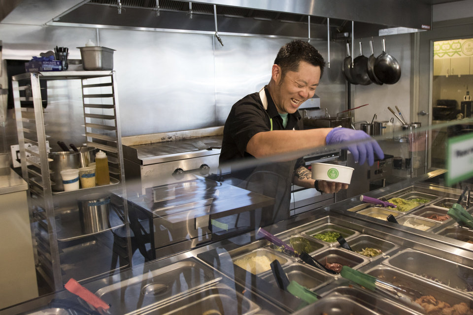Photo -  Dan Johnson, the assistant general manager at Gogi Go, adds ingredients to a bowl at the restaurant, a new fast-casual Korean restaurant in Oklahoma City. [Photo by Anya Magnuson, The Oklahoman]
