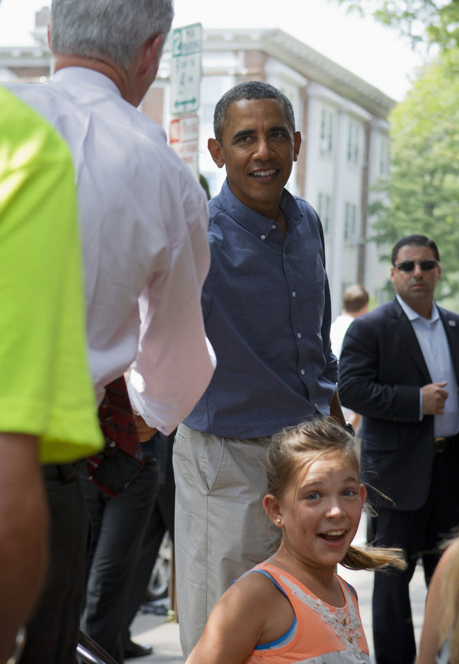 Photo - Rubi Platt, 11, of Orange County, Calif., reacts as President Barack Obama shakes hands behind her during his stop at Magnolia's Deli and Cafe in Rochester, N.Y., Thursday, Aug. 22, 2013, to talk with college students and their parents on the first day of a two-day bus tour where he is speaking about college financial aid. (AP Photo/Jacquelyn Martin)