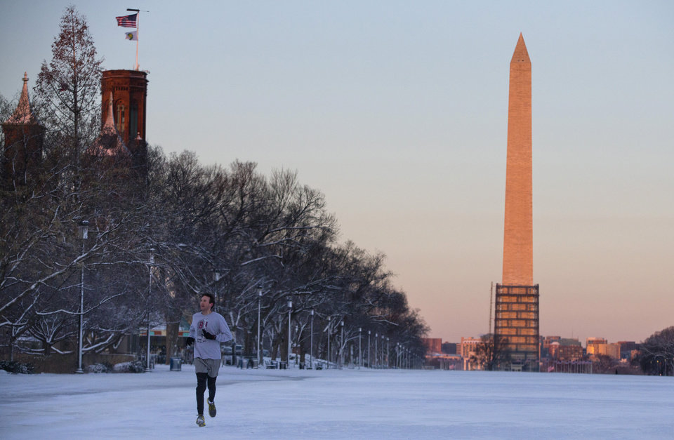 Photo - A jogger runs on the National Mall, with the Washington Monument in the background, Friday, Jan. 3, 2014, in Washington. After a storm blew through the Washington region overnight, roads are being cleared and many schools systems are closed. The federal government and the District of Columbia government will be open Friday, but workers have the option to take leave or telework.  (AP Photo/ Evan Vucci)