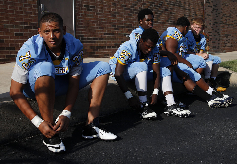 Photo - Putnam City West players lace up before a scrimmage at Putnam City West High School in Bethany, Thursday, Aug. 21, 2014.  Photo by Garett Fisbeck, For The Oklahoman