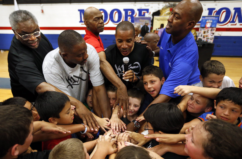 Photo - Former NBA All-Stars Otis Birdsong, with microphone, leads a huddle with (left to right) Sam Sibert, Michael Ray Richardson, Ron Brewer and Danny Manning as they host a basketball clinic for tornado victims on Thursday, June 13, 2013 in Moore, Okla.  Photo by Steve Sisney, The Oklahoman