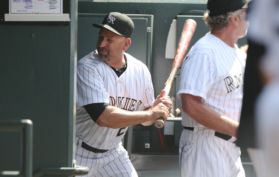 Photo - Upset after being ejected from the game, Colorado Rockies manager Walt Weiss takes a bat and smashes it into the wall by the batting rack in his team's dugout on his way to the showers against the Atlanta Braves in the eighth inning of the Rockies' 10-3 victory in a baseball game in Denver on Thursday, June 12, 2014. Weiss was upset over the Rockies' Corey Dickerson being hit by a pitch thrown by Braves relif pitcher David Carpenter. (AP Photo/David Zalubowski)