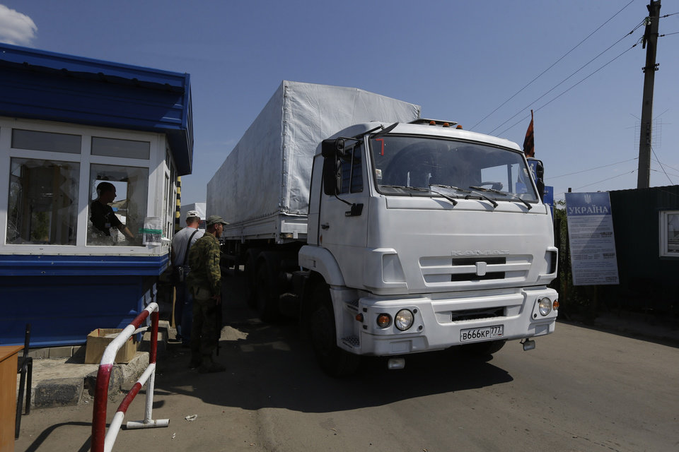 Photo - Ukrainian border guards look at the first truck as it passes the border post at Izvaryne, eastern Ukraine, Friday, Aug. 22, 2014. The first trucks in a Russian aid convoy crossed into eastern Ukraine on Friday, seemingly without Kiev's approval, after more than a week's delay amid suspicions the mission was being used as a cover for an invasion by Moscow. (AP Photo/Sergei Grits)