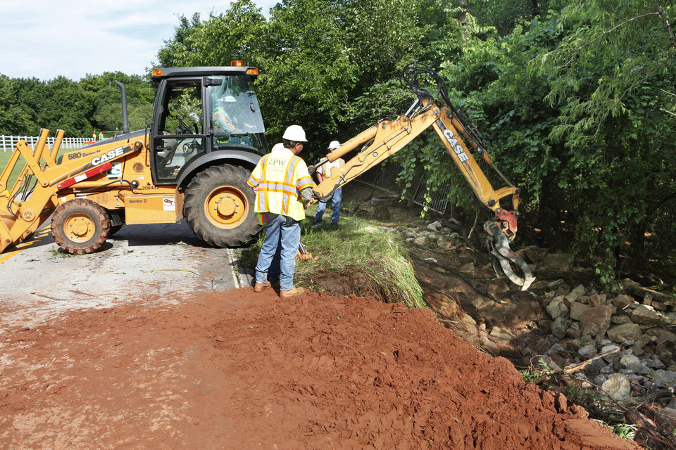 Photo - Edmond city workers attempt to rebuild the lost shoulder of Coffee Creek Rd. between Kelly and Santa Fe in Edmond, OK, after yesterday's torential rains. Tuesday, June 15, 2010. By Paul Hellstern, The Oklahoman