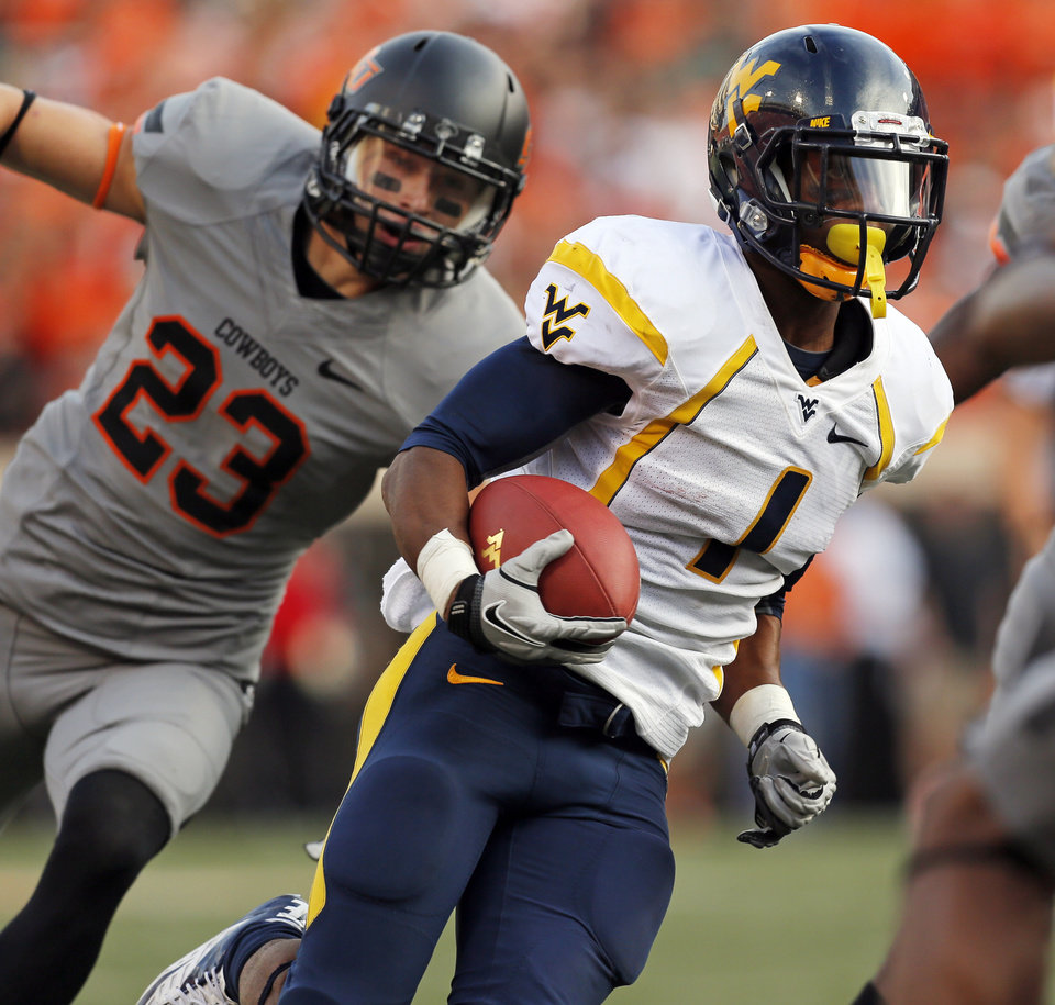 Photo - West Virginia's Tavon Austin (1) runs past Oklahoma State's Zack Craig (23) on his way to a touchdown in the second quarter during a college football game between Oklahoma State University (OSU) and West Virginia University (WVU) at Boone Pickens Stadium in Stillwater, Okla., Saturday, Nov. 10, 2012. Photo by Nate Billings, The Oklahoman