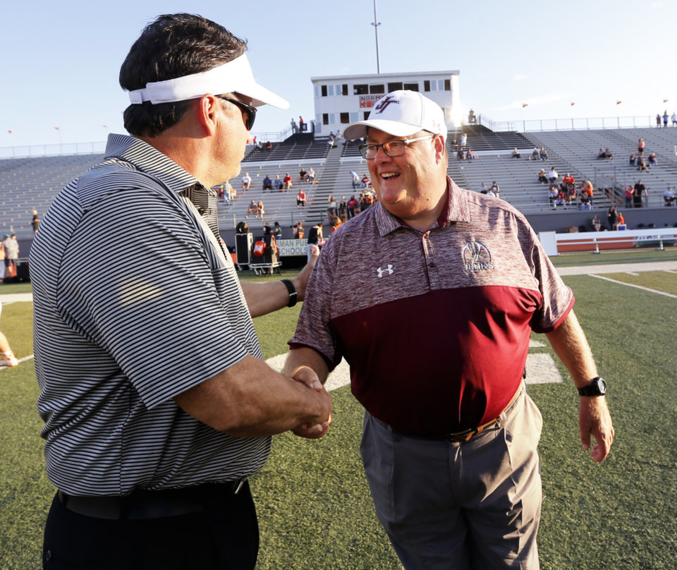 Photo - Jenks head coach Allan Trimble and Norman High head coach Greg Nation shake hands after the coin toss as the Jenks Trojans prepares to play the Norman High School Tigers on Friday, Sept. 23, 2016 in Norman, Okla. Photo by Steve Sisney, The Oklahoman