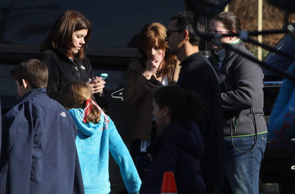 Photo - A woman weeps as she arrives to pick up her children at the Sandy Hook Elementary School in Newtown, Conn. where authorities say a gunman opened fire, leaving 27 people dead, including 20 children, Friday, Dec. 14, 2012. (AP Photo/The Journal News, Frank Becerra Jr.) MANDATORY CREDIT, NYC OUT, NO SALES, TV OUT, NEWSDAY OUT; MAGS OUT ORG XMIT: NYWHI109
