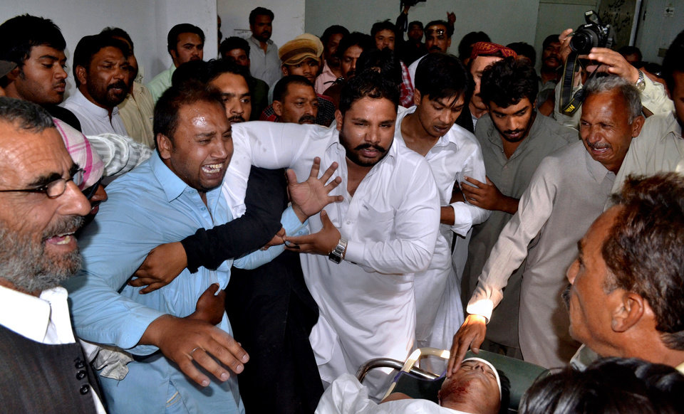 Photo - Pakistani men mourn over the lifeless body, bottom right, of a provincial lawmaker Handery Masieh at a local hospital in Quetta, Pakistan, Saturday, June 14, 2014. A guard for a provincial Christian lawmaker shot and killed the legislator during a meeting Saturday in southwest Pakistan, police said. Government spokesman Jan Mohammad Buledi said the guard fled after the attack and police were trying to arrest him.