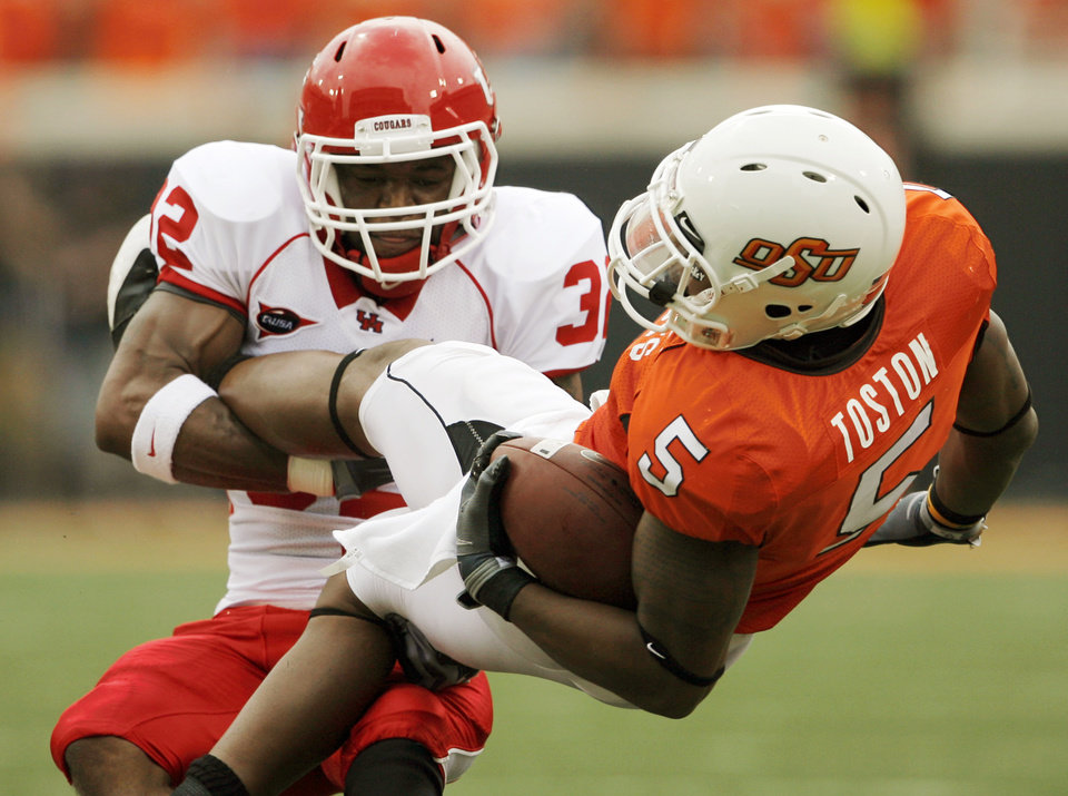 Photo - Houston's Jamal Robinson (32) takes down OSU's Keith Toston (5) after a catch in the second quarter during the college football game between the University of Houston (UH) Cougars and the Oklahoma State University (OSU) Cowboys at Boone Pickens Stadium in Stillwater, Okla., Saturday, September 12, 2009. Photo by Nate Billings, The Oklahoman ORG XMIT: KOD